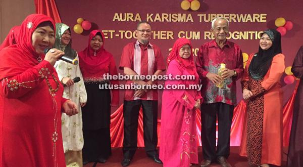 Salmah (kiri) memperkenalkan ahli keluarga Dollah Ali Zaini (dua kanan) yang telah memberi sokongan kuat kepada Aura Karisma.
