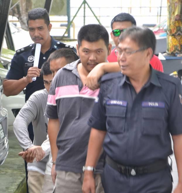Hii (dua kanan) diiring anggota polis selepas didakwa di Mahkamah Majistert atas tuduhan membunuh.