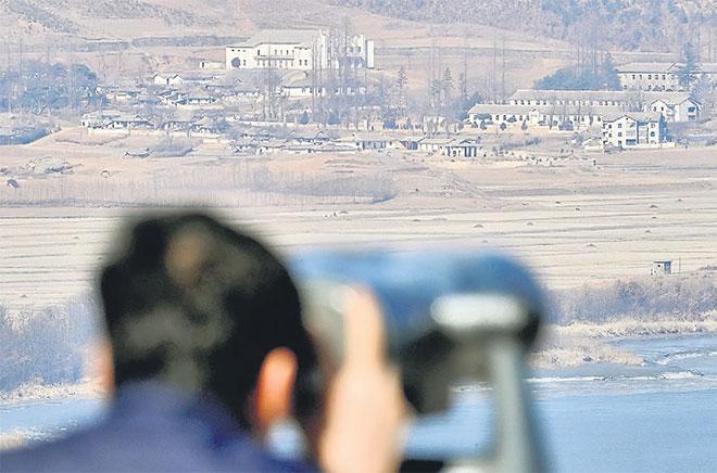 Seorang lelaki meneropong kampung propaganda Kaepoong dari pelantar tinjau dekat zon tanpa tentera yang memisahkan kedua-dua negara Korea di Paju, semalam. — Gambar Reuters