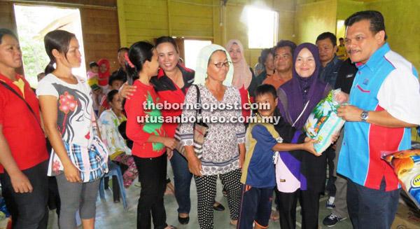 Ruzlan (kanan) menyampaikan beberapa kampit beras kepada ketua keluarga mangsa banjir di Dewan Kampung Masalog.