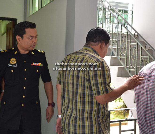 Wan Akil (kanan) diiringi oleh seorang pegawai SPRM keluar dari mahkamah setelah dijatuhkan hukuman atas tuduhan mengemukakan tuntutan elaun perjalanan palsu.