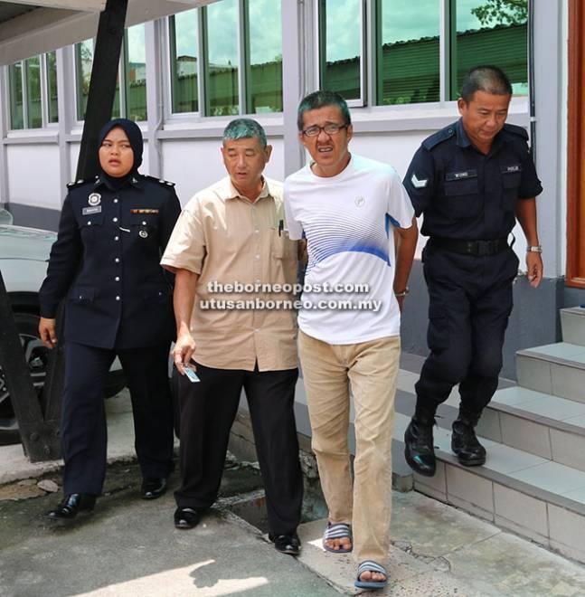 Amin (dua kanan) dibawa keluar dari mahkamah oleh anggota polis setelah dijatuhkan hukuman atas 22 pertuduhan menipu.