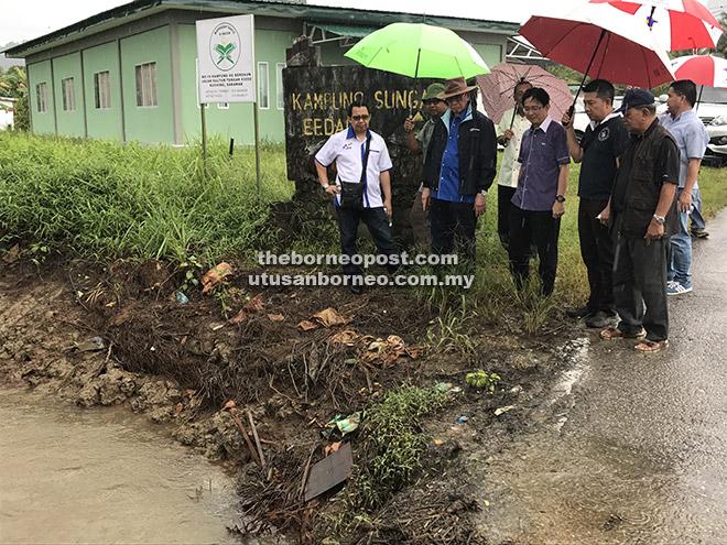 Wan Junaidi (tiga kiri) bersama wakil JPS dan ketua masyarakat ketika meninjau kawasan perparitan Kampung Sungai Bedaun Kuching, semalam.