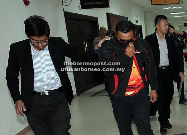 Tertuduh (kanan) dibawa keluar selepas sebutan pertuduhan di Mahkamah           Khas Rasuah di Kuching semalam.