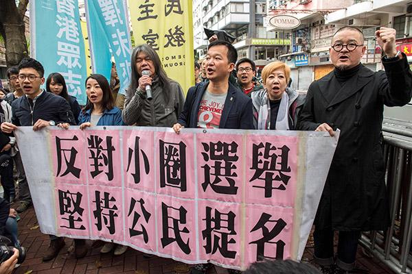 Wong (tiga kanan) menyertai para penunjuk perasaan yang berarak tanda protes ke lokasi pilihan raya ketua eksekutif di Hong Kong, kelmarin. — Gambar AFP