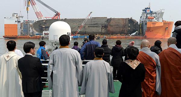 Orang ramai dan ahli keluarga mangsa tragedi feri menyaksikan operasi menyelamat bangkai kapal luar pantai pulau selatan Jindo, kelmarin. — Gambar AFP