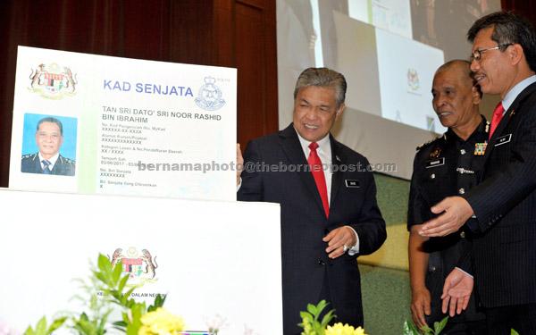 Ahmad Zahid (kiri) melancarkan kad senjata pada Perhimpunan Bulanan Kementerian Dalam Negeri (KDN) semalam. — Gambar Bernama
