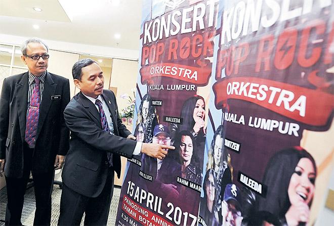 Anwar (kanan) menunjukkan poster Konsert Pop Rock Orkestra Kuala Lumpur yang akan berlangsung pada 15 April ini secara percuma di Panggung Anniversari Taman Botani. — Gambar Bernama