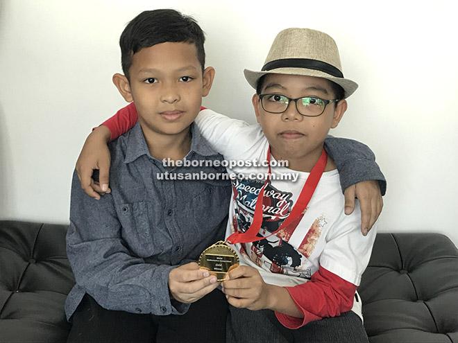 (Dari kiri) Najmi dan Jad menunjukkan pingat emas diperolehi mereka.