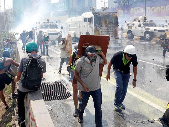 Penunjuk perasaan bertempur dengan pasukan keselamatan ketika perhimpunan menentang Maduro di Caracas, Venezuela pada 10 Mei. — Gambar Reuters