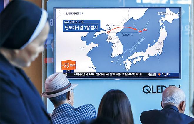 Orang ramai menonton laporan berita mengenai ujian misil balistik Korea Utara di sebuah stesen kereta api di Seoul, semalam. — Gambar Reuters