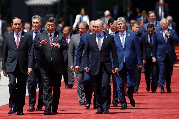 Xi berbual dengan rakan sejawatannya dari Vietnam Tran Dai Quang (kiri) sambil diperhatikan Putin semasa mereka tiba bersama para pemimpin lain untuk foto keluarga forum tersebut yang diadakan di pusat persidangan antarabangsa di TasiK Yanqi, utara Beijing semalam. — Gambar AFP