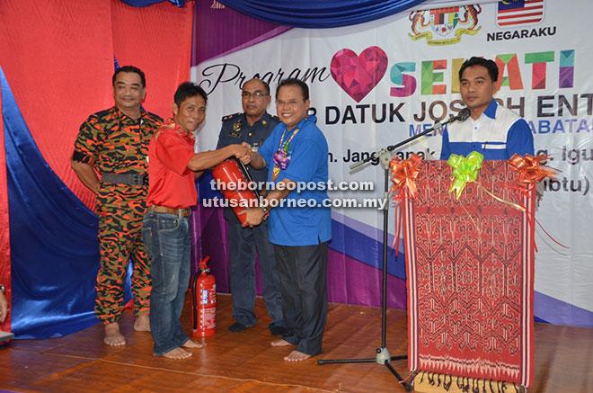 Entulu (empat kiri) menyerahkan alat pemadam api kepada salah         seorang tuai rumah sambil diperhatikan oleh Ketua Jabatan Bomba dan Penyelamat Malaysia (JBPM) Zon Sibu Abdul Mutalib Rashid (tiga kiri).