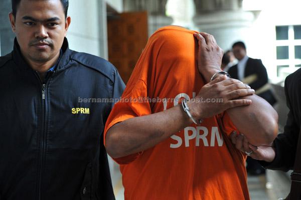 Pegawai Suruhanjaya Pencegahan Rasuah Malaysia (SPRM) mengiringi seorang anggota polis berpangkat koperal yang bertugas di Ibu Pejabat Polis Kontinjen Melaka untuk perintah reman di Mahkamah Magistret, Putrajaya, semalam. — Gambar Bernama