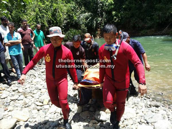 Pihak bomba mengangkat mayat mangsa dari tebing sungai sebelum diserah kepada pihak polis.