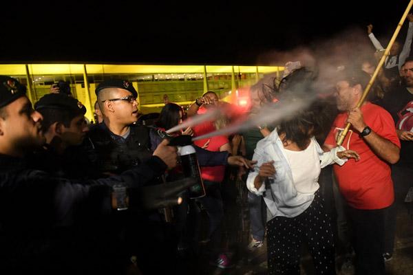 Penunjuk perasaan disembur dengan semburan lada oleh polis ketika demonstrasi terhadap Temer di Brasilia kelmarin. — Gambar AFP/Reuters