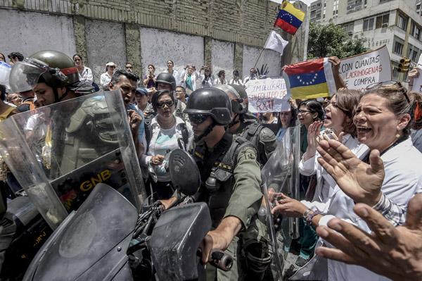 Doktor dan jururawat melaungkan slogan di hadapan anggota Pengawal Negara ketika demonstrasi di Caracas kelmarin. — Gambar AFP