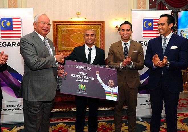 Najib menyampaikan kad akses satu unit suite kediaman di Trion 888 SoHo kepada Azizulhasni yang merangkul gelaran Johan Keirin Dunia pada satu majlis di Seri Perdana, Putrajaya, semalam. — Gambar Bernama