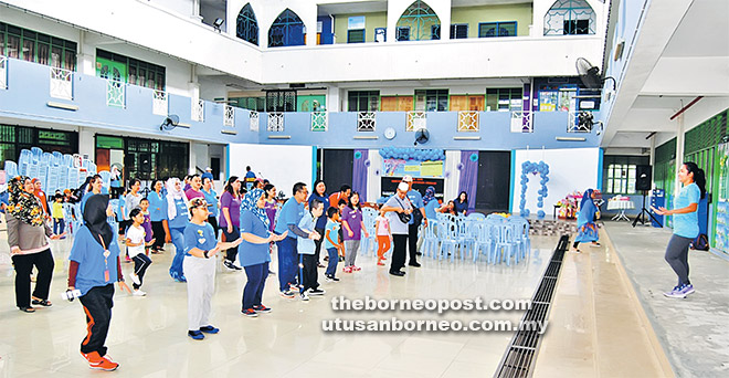 Sebahagian kanak-kanak autisme dan penjaga mereka menyertai acara senaman sebelum upacara perasmian bermula pada paginya.