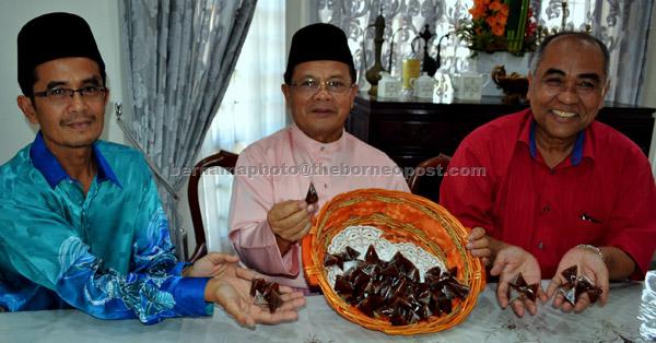 Ahmad (tengah) menunjukkan dodol yang dihasil menggunakan campuran santan kelapa dan santan sawit ketika ditemui pemberita selepas Majlis Rumah Terbuka Aidilfitri di rumahnya di Jasin, kelmarin. Turut hadir Ahmad Kushairi (kanan). — Gambar Bernama