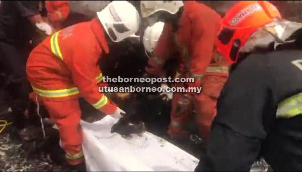 Bomba mengangkat mayat mangsa dari bawah pacuan empat roda sejurus api berjaya dikawal.