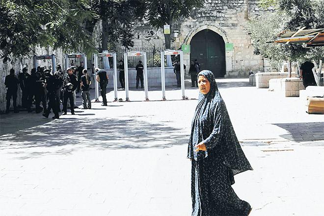 Seorang wanita Palestin melintas ketika anggota polis rejim memasang alat pengesan logam di luar Pintu Singa, pintu masuk utama ke kompleks Masjidil Aqsa di Kota Lama Baitulmaqdis, semalam. — Gambar AFP