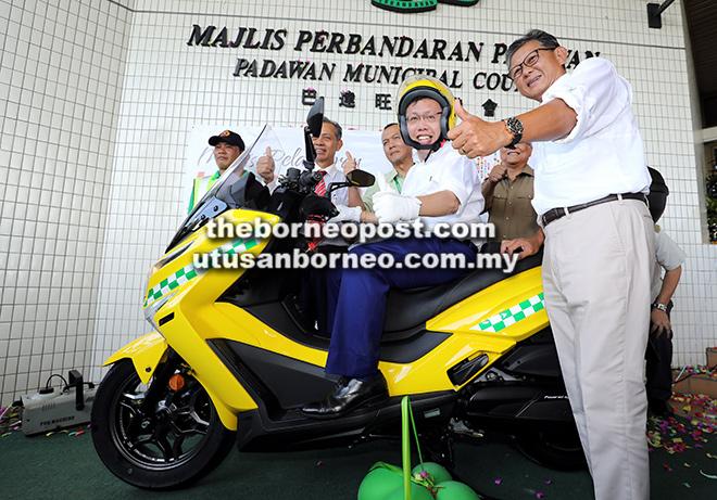 Dr Sim mencuba motosikal yang diserahkan kepada  skuad LA Serve MPP. Turut kelihatan (dari kanan) Bakrie, Minos, Ahmad dan Penguang.