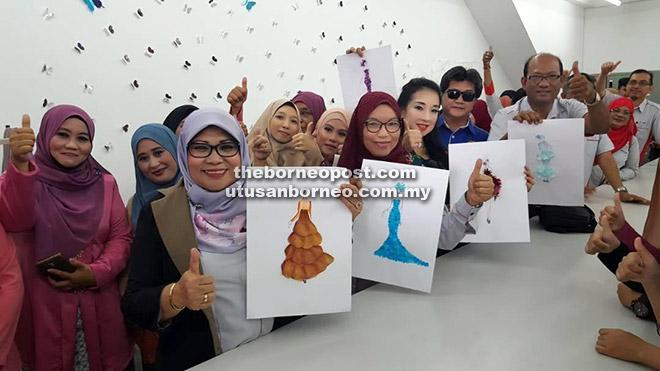 Rohani (dua kiri) ditemani peserta Pusat Fesyen Wanita Beladin menunjukkan reka bentuk pakaian yang akan dihasilkan di situ.