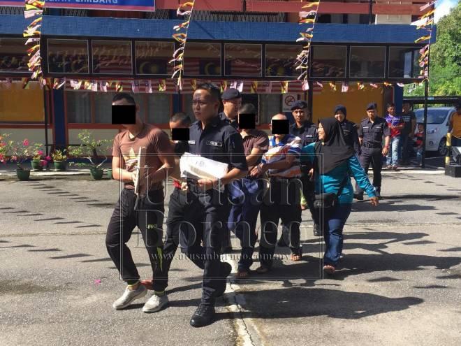 Tertuduh diiringi anggota polis menuju ke Mahkamah Majistret Limbang pagi tadi.