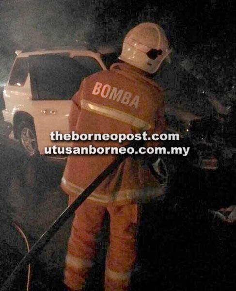 Anggota bomba berusaha memadamkan api di bahagian enjin kereta dalam kemalangan di Jalan Pending.