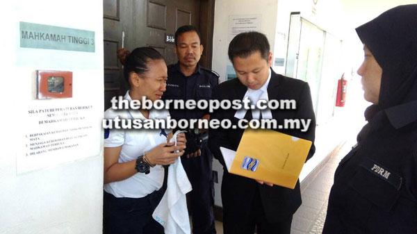 Rubiah (kiri) bersama peguamnya Hairul di luar mahkamah.