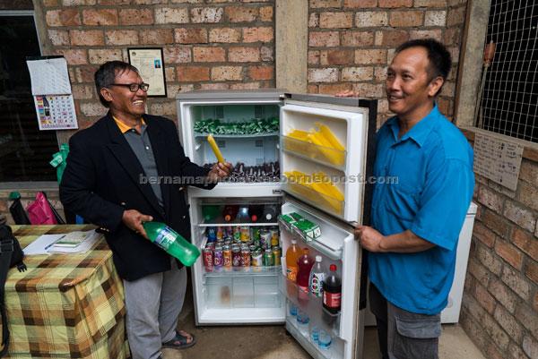 Patrick (kanan) menunjukkan peti sejuk yang kini ditempatkan di kedai runcit miliknya sejak sistem tenaga hidro mikro di bawah projek iM Sarawak membekalkan elektrik 24 jam secara percuma di Kampung Long Semadoh Rayeh. — Gambar Bernama