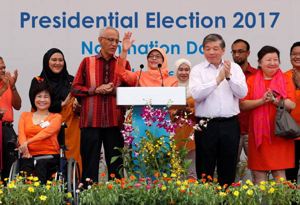 Halimah berucap di hadapan para penyokongnya sambil diperhatikan suaminya Mohammed Abdullah Alhabshee (tiga kiri) sebelum meninggalkan pusat penamaan calon di Singapura, semalam. — Gambar Reuters