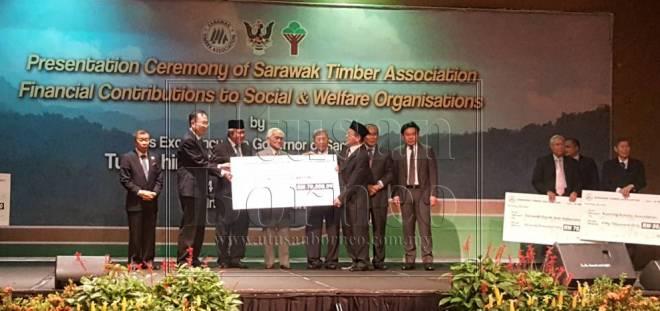 Tun Taib menyampaikan replika cek sumbangan kepada penerima sambil disaksikan Lau (dua kiri), Awang Tengah serta tetamu jemputan lain pada majlis penyampaian sumbangan hari ini.
