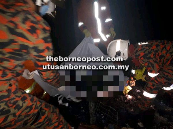 Anggota bomba mengangkat mayat mangsa dari tempat kejadian untuk dihantar ke HUS.