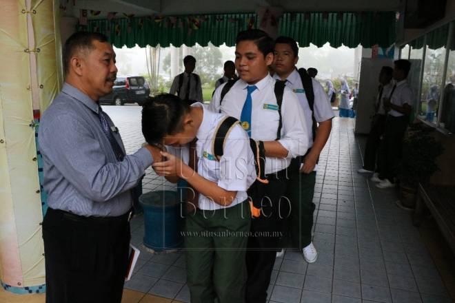 Antara 401 calon Pentaksiran Tingkatan Tiga dari Sekolah Menengah Kebangsaan Kota Samarahan bersalaman dengan pengetua mereka, Bujang Awang Jamain sebelum masuk ke bilik peperiksaan.