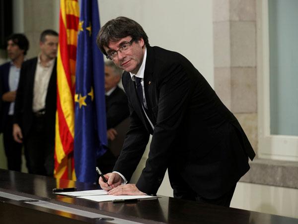 Puigdemont menandatangani pengisytiharan kemerdekaan di Parlimen Catalonia di Barcelona, kelmarin. — Gambar Reuters