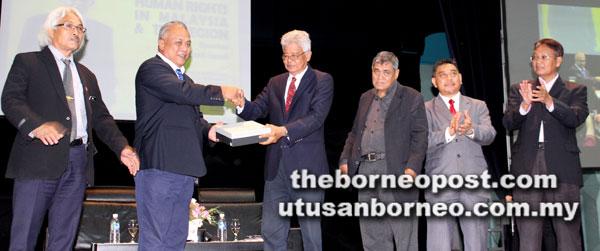 Timbalan Naib Canselor (Penyelidik dan Inovasi) UMS Prof Dr Shahril Yusof (dua kiri) menyampaikan cenderamata kepada Razali (tiga kiri), sambil diperhatikan oleh barisan tetamu kehormat lain.