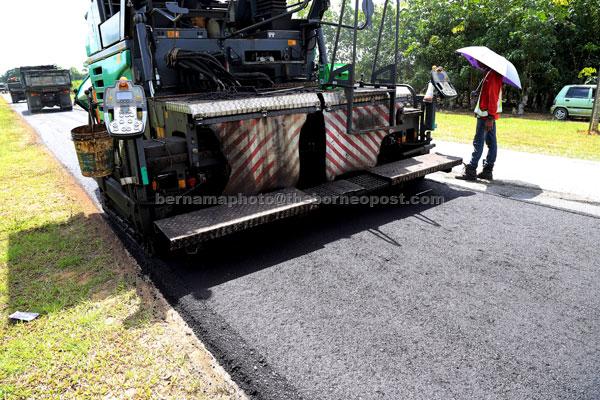 Kerja penurapan jalan di bawah projek perintis pembinaan jalan menggunakan getah di Stesen Penyelidikan Lembaga Getah Malaysia Kota Tinggi Johor. — Gambar Bernama
