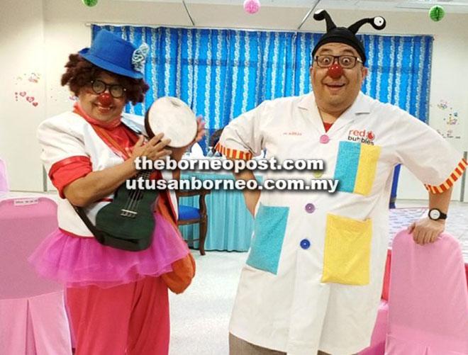 Normah (kiri) dan rakannya menjadi badut hospital untuk menghiburkan kanak-kanak yang sakit tenat di hospital. — Gambar oleh Normah Nordin