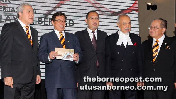 Abang Johari (dua kiri) menunjukkan setem yang dilancarkan. Turut kelihatan (dari kanan) Uggah, Asfia, Jailani dan Awang Tengah.