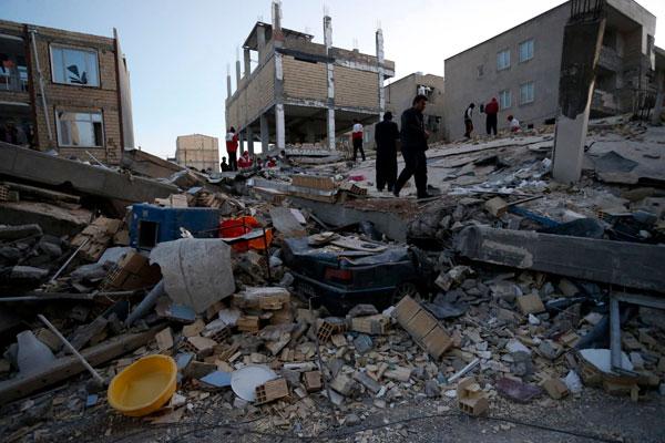 Kakitangan penyelamat dibantu penduduk tempatan menjalankan operasi mencari dan menyelamat susulan gempa bumi di Sarpol-e Zabah di Kermanshah, semalam manakala gambar kanan memaparkan orang ramai menunjukkan reaksi terkejut sejurus gegaran dirasai di situ. — Gambar AFP/Reuters