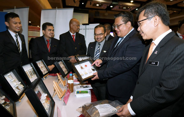 Nur Jazlan Mohamed (dua, kanan) melihat sebahagian dadah yang dipamerkan sempena Majlis Perasmian Konvensyen Perangi Dadah Kebangsaan yang di adakan di Dewan Tunku Canselor Universiti Sains Islam Malaysia (USIM) semalam. — Gambar Bernama