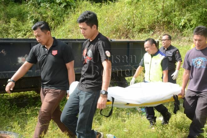 Mayat mangsa diangkat anggota polis untuk dibawa ke rumah mayat Hospital Limbang untuk bedah siasat.