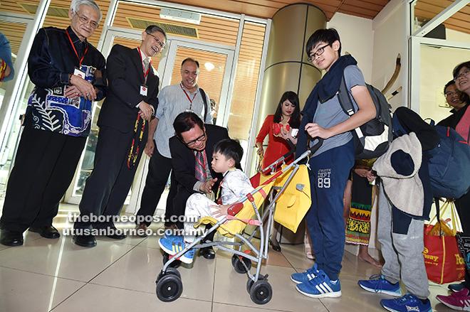 Lee turut beramah dengan penumpang kanak-kanak yang menaiki penerbangan AirAsia Shenzhen yang pertama tiba di LTAK, semalam. Turut kelihatan Zhang (dua kiri) dan Wahab (kiri).