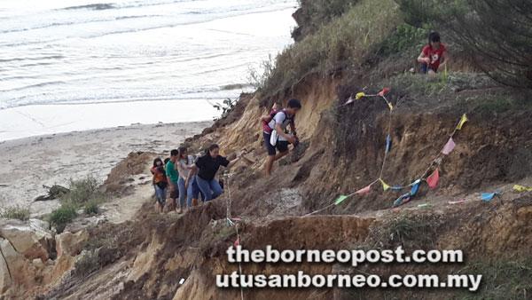Beberapa pelawat berkunjung ke Pantai Tusan memberanikan diri naik ke atas tebing selepas tangga runtuh.