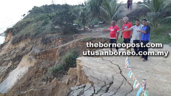 Mansor (dua kanan) dan Yusri menunjukkan laluan pejalan kaki runtuh di Pantai Tusan menyebabkan pelawat terkandas di atas tebing.