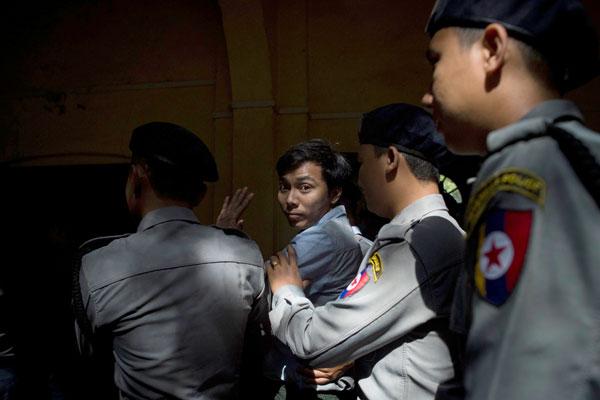 Kyaw Soe Oo diiringi polis selepas didakwa secara rasmi di bawah OSA di mahkamah di Yangon semalam. — Gambar AFP