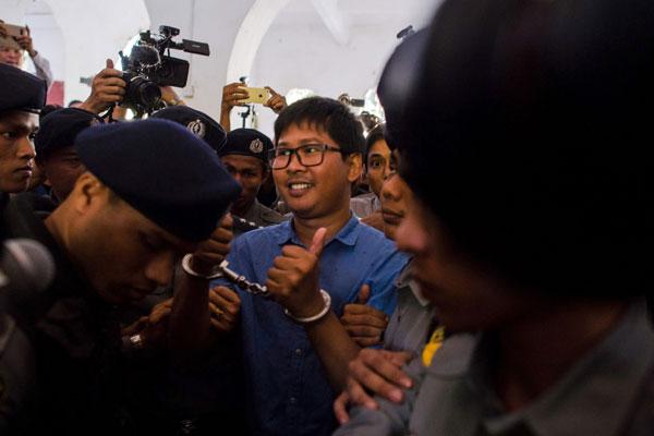 Wa Lone diiringi polis selepas didakwa secara rasmi di bawah OSA di mahkamah di Yangon semalam. — Gambar AFP