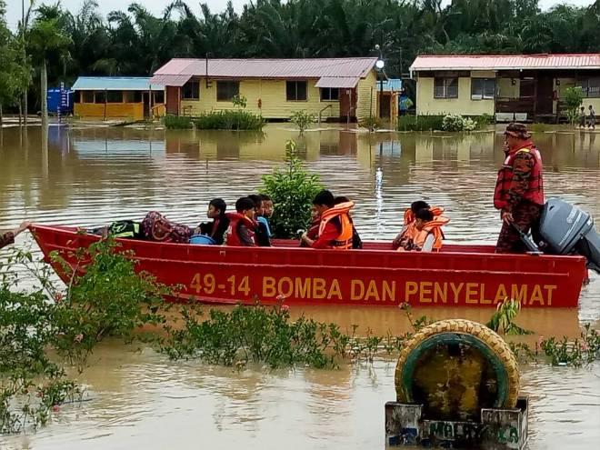 Anggota bomba dan penyelamat membantu mangsa banjir.